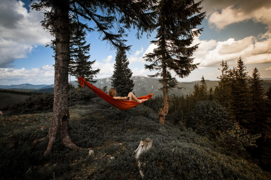 person lying on red hammock