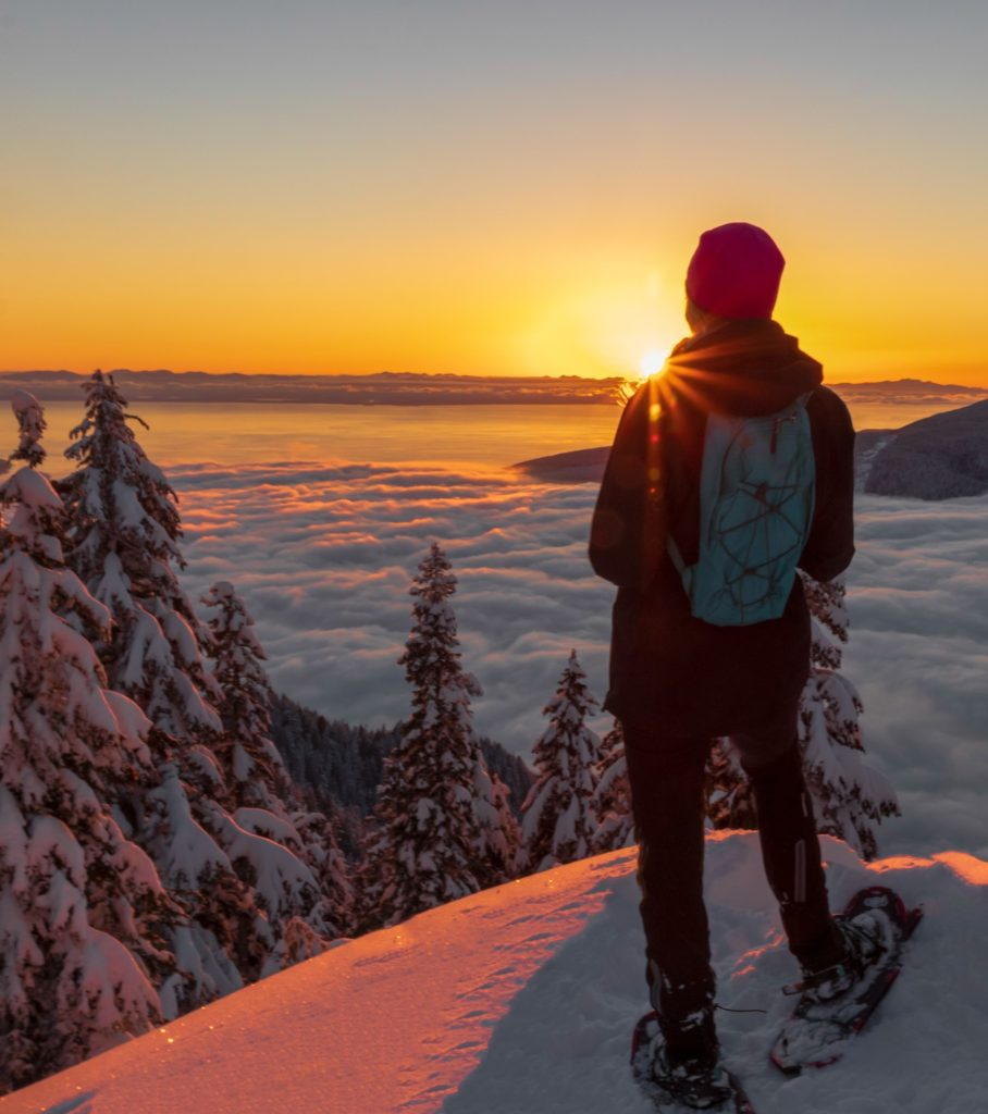 woman in black pants standing on snow covered ground during sunset