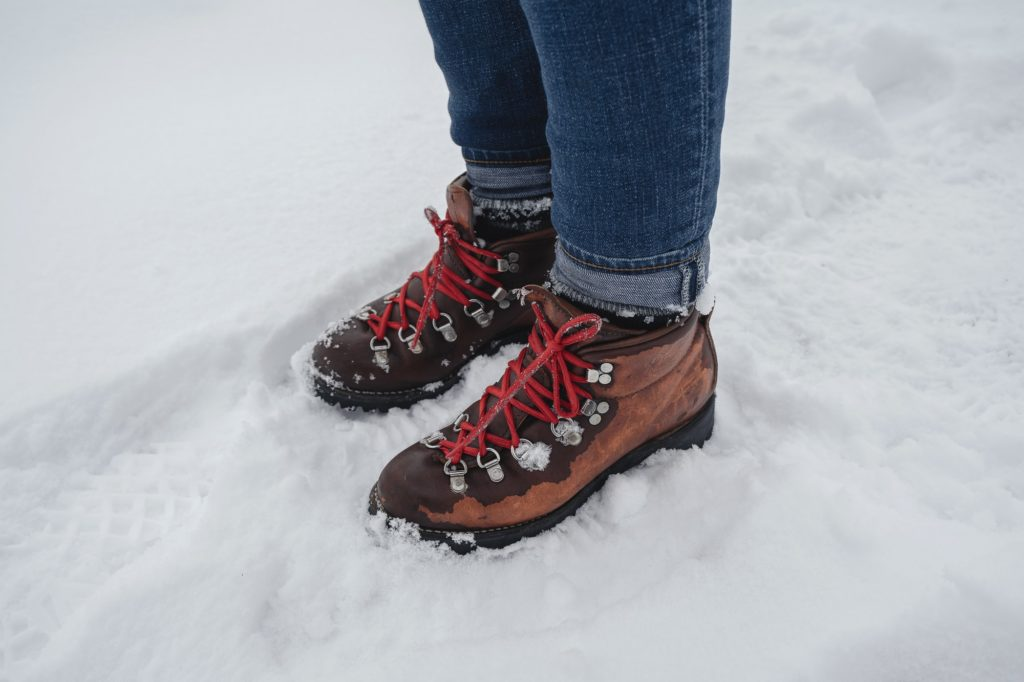 person in blue denim jeans and brown leather boots standing on snow covered ground during daytime