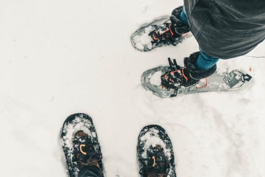 person in black pants and black and white snow ski shoes standing on snow covered ground